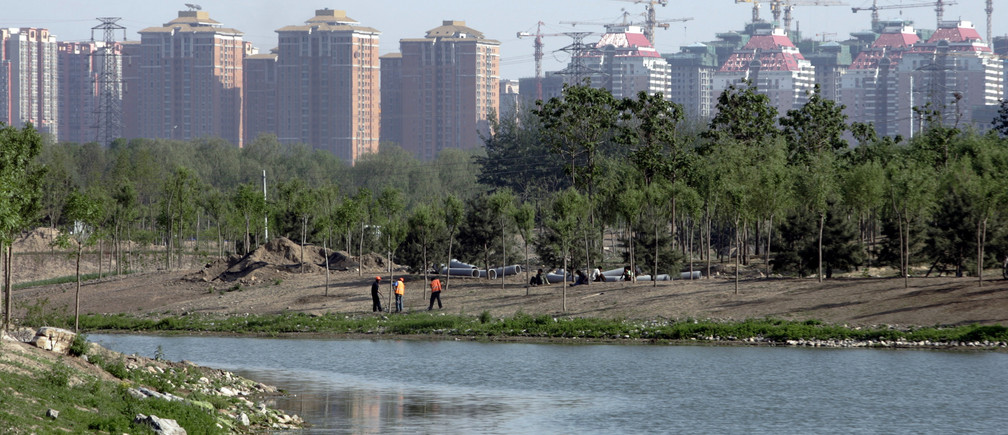Workers plant trees near a river inside the Olympic Park, which is under construction, in Beijing May 9, 2007. REUTERS/Jason Lee (CHINA) - RTR1PHTQ