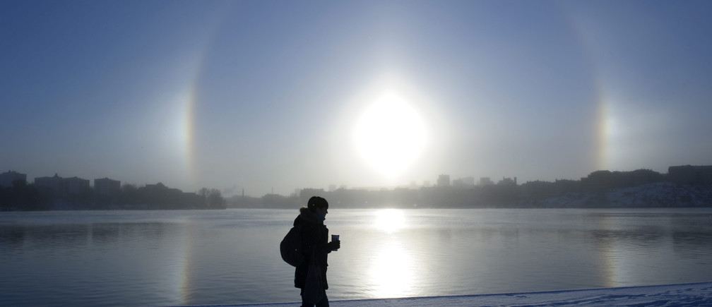 A parhelion (sundog) combined with a halo is seen over Lake Malaren in central Stockholm November 30, 2010. These weather phenomena are created by ice crystals in the atmosphere during cold weather. Stockholm is presently experience temperatures below minus 10 degree Celsius (14 degrees Fahrenheit).  REUTERS/Henrik Montgomery/Scanpix (SWEDEN - Tags: ENVIRONMENT IMAGES OF THE DAY) THIS IMAGE HAS BEEN SUPPLIED BY A THIRD PARTY. IT IS DISTRIBUTED, EXACTLY AS RECEIVED BY REUTERS, AS A SERVICE TO CLIENTS. SWEDEN OUT. NO COMMERCIAL OR EDITORIAL SALES IN SWEDEN - GM1E6BU1IJQ01