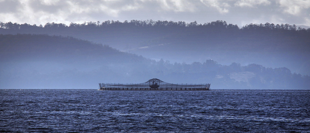 A netted pond, which can hold up to 40,000 fish, is seen floating on Hideaway Bay at a Tasmanian salmon farm