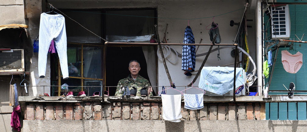 Un hombre mayor se asoma al balcón en Wuhan, el epicentro del brote de COVID-19, provincia de Hubei, China.