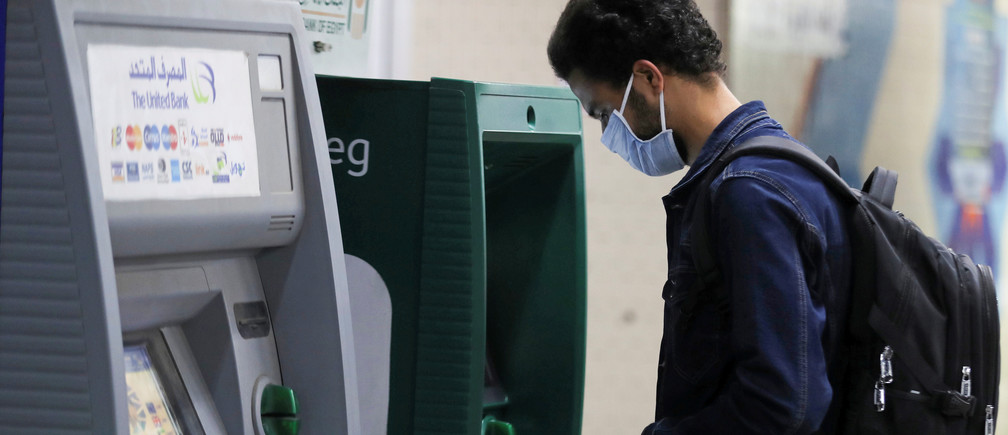 "A man wearing protective face mask withdraws money from an ATM at the underground Al Shohadaa ""Martyrs"" metro station while Egypt ramps up its efforts to slow down the spread of the coronavirus disease (COVID-19) in Cairo, Egypt March 22, 2020."