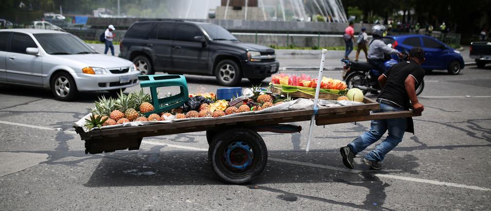 A fruit seller pulls his cart in Guatemala City, Guatemala.