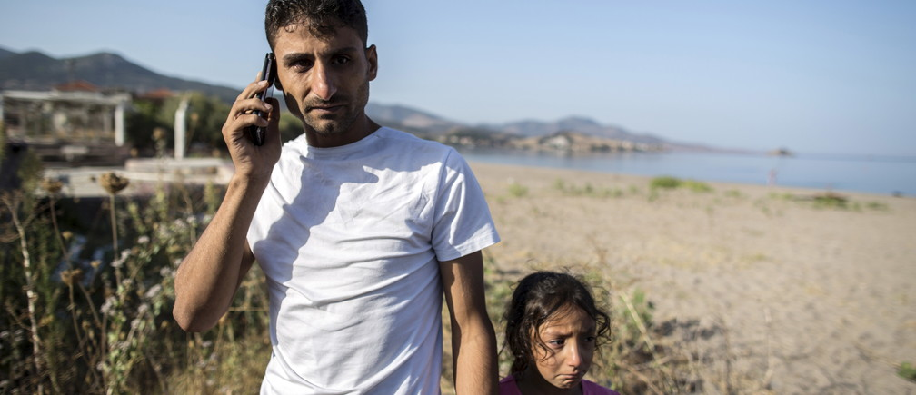 Ihab, a 30-year-old Syrian migrant from Deir Al Zour, reacts as he talks on the phone with his mother, who has been a refugee in Germany for two months, at the beach after arriving on the Greek island of Lesbos September 11, 2015. The crossing from Turkey and the eventual trip to Athens is only the beginning for Ihab and other families. Ahead lies a trek north through Greece, up via Macedonia and Serbia to Hungary and on to Austria, Germany and more industrialised countries. Picture taken September 11, 2015. REUTERS/Zohra Bensemra - RTS1518