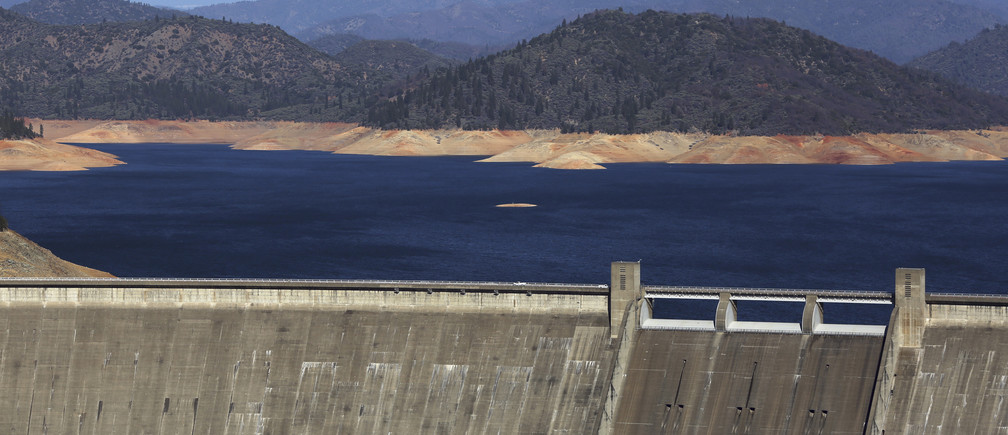 Shasta Lake, which is 100 feet (30 meters) below its normal levels, is shown behind Shasta Dam with Mount Shasta in background  in Shasta, California January 23, 2014. California Governor Jerry Brown last week declared a drought emergency, and the dry year of 2013 has left fresh water reservoirs with a fraction of their normal water reserves. Picture taken January 23, 2014.  REUTERS/Robert Galbraith (UNITED STATES - Tags: ENVIRONMENT) - GM1EA1P0B4K01