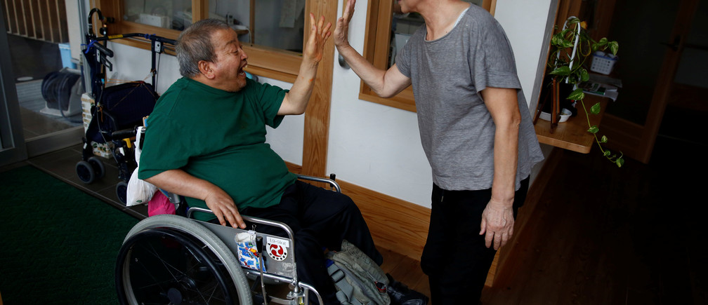 Congenital Minamata disease patient Isamu Nagai high-fives a caretaker as he arrives at Oruge-Noa, a group care home for disabled people including Minamata disease patients, in Minamata, Kumamoto Prefecture, Japan, September 13, 2017. Nagai was born in 1957 and cannot walk due to congenitally deformed legs