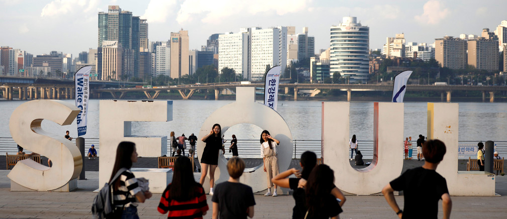 Tourists pose for photographs at the Han river park in Seoul, South Korea, August 1, 2017.  REUTERS/Kim Hong-Ji - RC1170B590D0