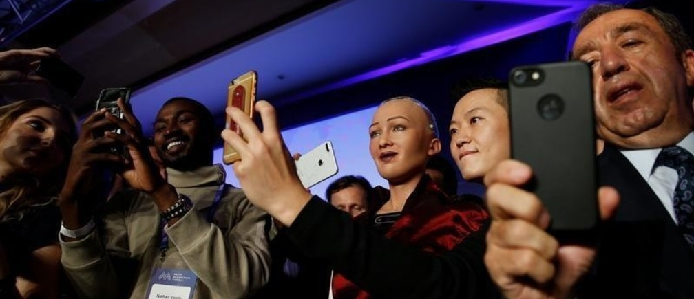 People take selfies with the humanoid robot Sophia, a creation of Hanson Robotics, at the Malta Blockchain Summit in St Julian's, Malta November 1, 2018. REUTERS/Darrin Zammit Lupi - RC15D5391AF0