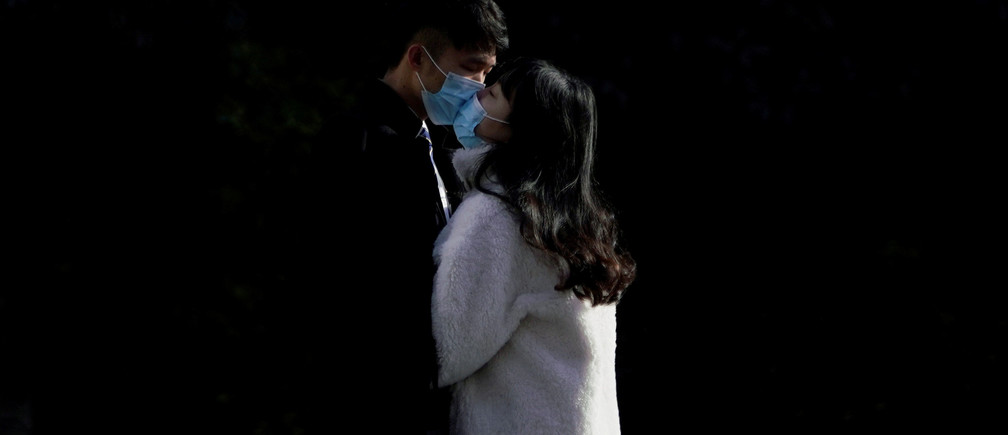 A couple wearing masks kiss at a main shopping area, in downtown Shanghai, China, as the country is hit by an outbreak of a new coronavirus, February 16, 2020.