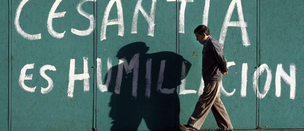 "A man walks past graffiti that reads ""unemployment is humiliation"" in downtown Santiago February 11,2009.  REUTERS/Ivan Alvarado (CHILE) - RTXBHNU"