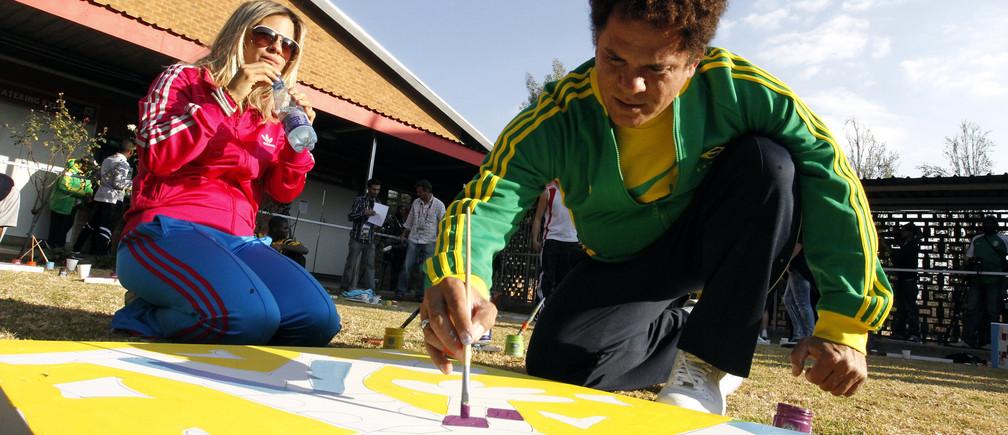 El icono de la cultura pop brasileña Romero Britto pinta en un taller para promover Football for Hope, un programa que utiliza el poder del fútbol para el desarrollo social, en la Queen's High School de Johannesburgo el 30 de junio de 2010.