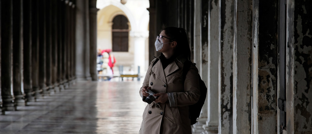 A woman wearing a protective face mask walks through St. Mark's Square after the Italian government imposed a virtual lockdown on the north of Italy including Venice to try to contain a coronavirus outbreak, in Venice, Italy, March 9, 2020. REUTERS/Manuel Silvestri - RC2GGF952R50