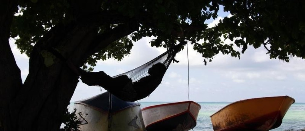 A man sleeps in a hammock next to fishing boats in the town of Bairki on South Tarawa in the central Pacific island nation of Kiribati May 23, 2013.   REUTERS/David Gray     (KIRIBATI - Tags: ENVIRONMENT SOCIETY POLITICS) - LM2E96B15FC01