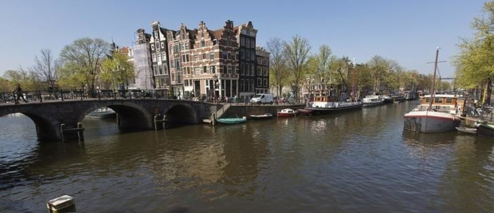 A view of one of the most photographed buildings at the intersection of Prinsengracht and Brouwersgracht canal in Amsterdam April 24, 2013. The Royal celebrations in the Netherlands this week put the country and the capital Amsterdam on front pages and television screens around the world with an orange splash. There's plenty to see and do in 48 hours in this compact city, where the world-famous Rijksmuseum only recently reopened after an extensive renovation. Picture taken April 24, 2013.  To match story TRAVEL-AMSTERDAM/  REUTERS/Michael Kooren (NETHERLANDS - Tags: TRAVEL SOCIETY)