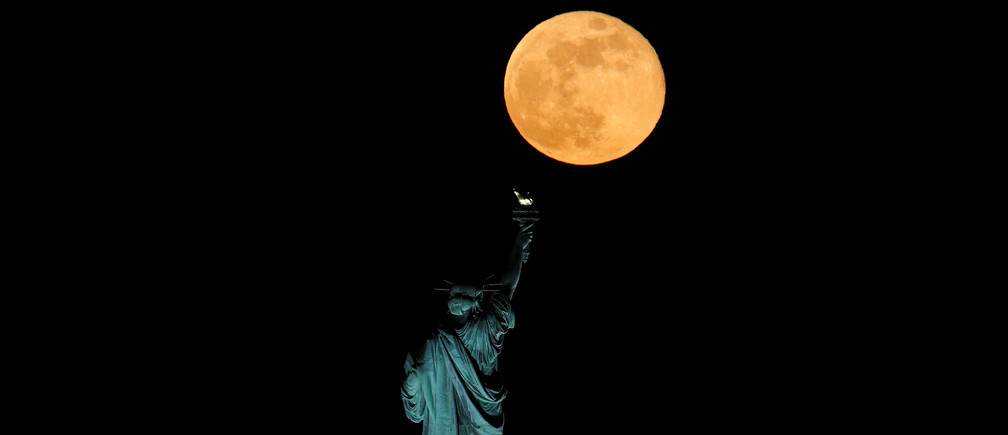 The full moon, also known as the Supermoon or Flower Moon, rises above the Statue of Liberty, as seen from Jersey City, New Jersey, U.S., May 7, 2020. REUTERS/Brendan McDermid - RC21KG918JB1