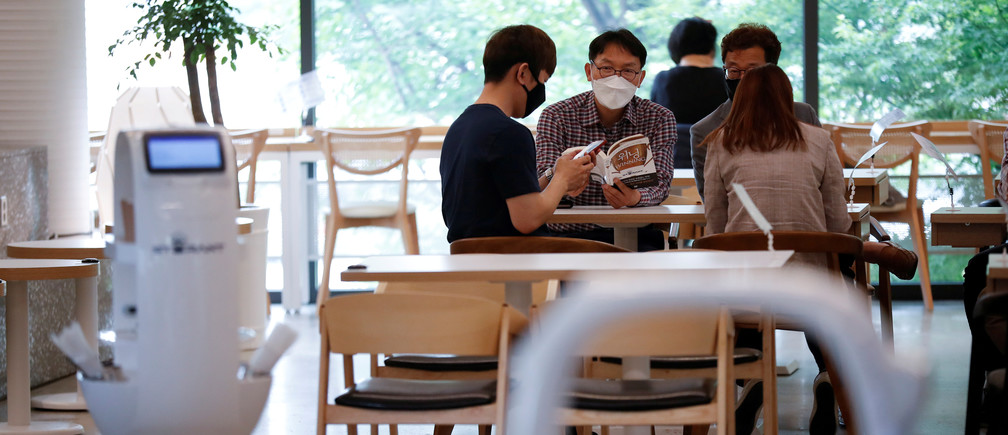 Customers wait at a cafe where a robot that takes orders, makes coffee and brings the drinks straight to customers is being used in Daejeon, South Korea, May 25, 2020. REUTERS/Kim Hong-Ji - RC2FVG9HKKJ0