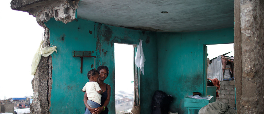 """Nathalie Pierre, 28, poses for a photograph with her daughter Rose, 3, in their destroyed house after Hurricane Matthew hit Jeremie, Haiti, October 17, 2016. """"As you can see, my situation is very bad. I lost all I had; my house, my money, my boutique. Everything gone in a few minutes. The storm was terrible but I was lucky to have my only daughter alive - that's the most important thing. Life goes on,"""" said Pierre. REUTERS/Carlos Garcia Rawlins          SEARCH """"HAITI PORTRAITS"""" FOR THIS STORY. SEARCH """"WIDER IMAGE"""" FOR ALL STORIES.  - RTX2T057"""