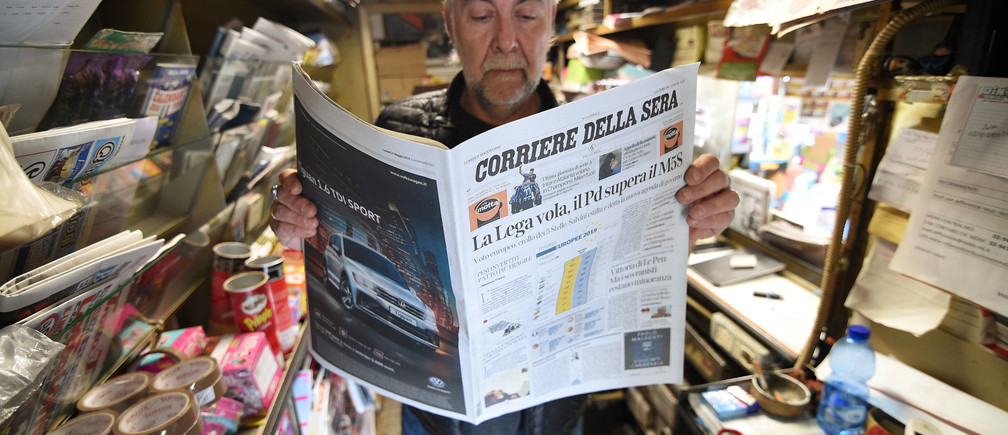 """A man reads a newspaper with news of the rise of the far-right League party in Sunday's European parliamentary election in Milan, Italy, May 27, 2019. The title reads """"The League flies, PD (Democratic Party) surpasses the 5-Star Movement"""" . REUTERS/Guglielmo Mangiapane - RC114FDAF3B0"""
