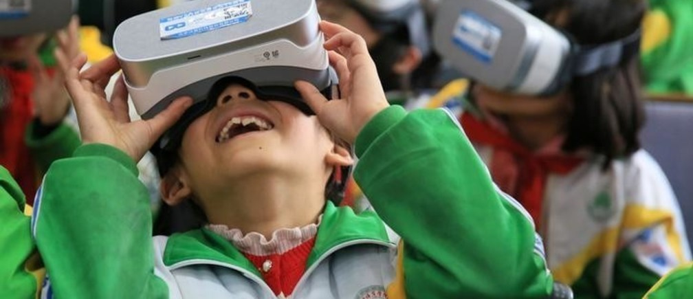 Primary school students wear virtual reality (VR) headsets inside a classroom in Xiangxi Tujia and Miao Autonomous Prefecture, Hunan province, China March 14, 2018. Picture taken March 14, 2018. REUTERS/Stringer  ATTENTION EDITORS - THIS IMAGE WAS PROVIDED BY A THIRD PARTY. CHINA OUT.