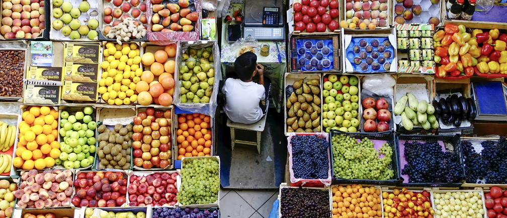 A boy takes a meal break at a fruit stall in the central market in Kazan, Russia, August 11, 2015.