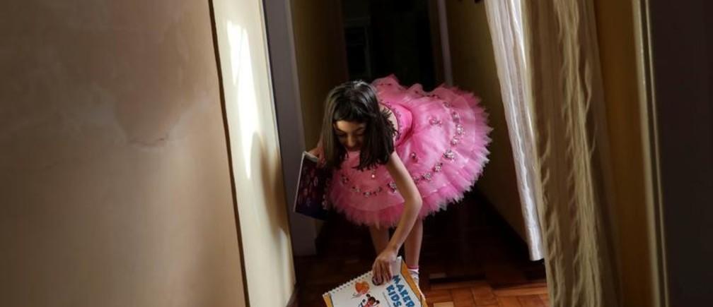 Alice, de 5 años, toma su libro del suelo después de su sesión de estudio en casa durante la cuarentena impulsada por el gobierno en Brasil.