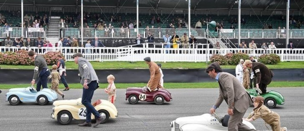 Parents assist  whilst children prepare to compete in a pedal car race as motoring enthusiasts attend the Goodwood Revival, a three day classic car racing festival celebrating the mid-twentieth century heyday of the sport, at Goodwood in southern Britain, September 9, 2018. REUTERS/Toby Melville