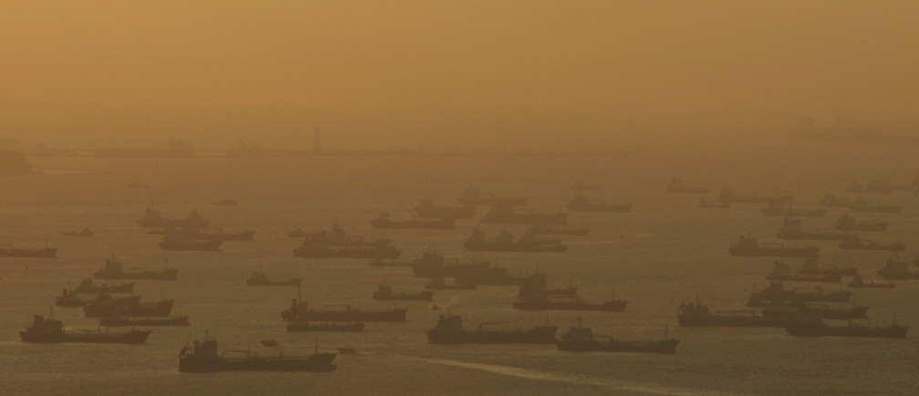 Shipping vessels and oil tankers line up the eastern coast of Singapore.
