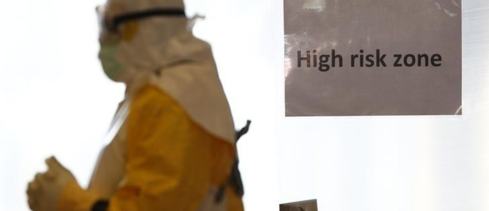A volunteer wearing a protective suit walks in a 'high risk' zone during an Ebola training session held by Germany's Red Cross in Wuerzburg October 21, 2014. The German Red Cross is training volunteer doctors, nurses and engineers to fight Ebola in western Africa.        REUTERS/Michaela Rehle (GERMANY  - Tags: HEALTH POLITICS TPX IMAGES OF THE DAY)