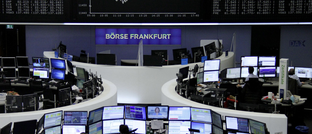 Traders work at their desks in front of the German share price index, DAX board, at the stock exchange in Frankfurt, Germany, December 27, 2016.      REUTERS/Staff/Remote - RTX2WLQI