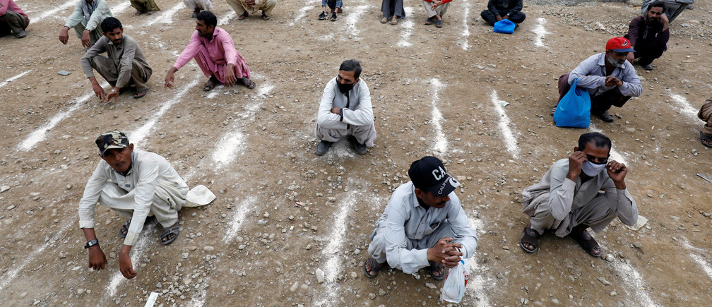Men sit on the ground with lines drawn with chalk to maintain safe distance as they wait to receive sacks of ration handouts from a distribution point of a charity welfare during a partial lockdown after Pakistan shut all markets, public places and discouraged large gatherings amid an outbreak of coronavirus disease (COVID-19), in Karachi, Pakistan, March 26, 2020. Coronavirus china virus health healthcare who world health organization disease deaths pandemic epidemic worries concerns Health virus contagious contagion viruses diseases disease lab laboratory doctor health dr nurse medical medicine drugs vaccines vaccinations inoculations technology testing test medicinal biotechnology biotech biology chemistry physics microscope research influenza flu cold common cold bug risk symptomes respiratory china iran italy europe asia america south america north washing hands wash hands coughs sneezes spread spreading precaution precautions health warning covid 19 cov SARS 2019ncov wuhan sarscow wuhanpneumonia  pneumonia outbreak patients unhealthy fatality mortality elderly old elder age serious death deathly deadly