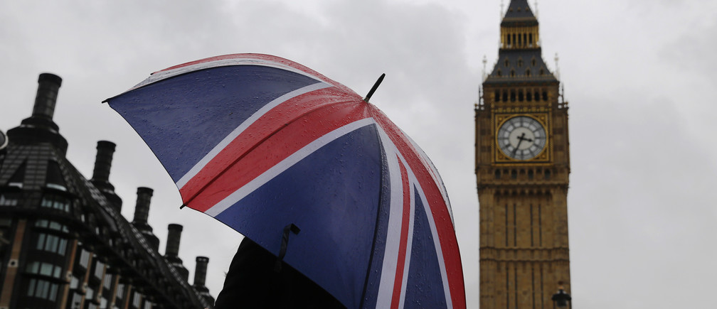A woman holds a Union flag umbrella in front of the Big Ben clock tower (R) and the Houses of Parliament in London October 4, 2014.  REUTERS/Luke MacGregor  (BRITAIN - Tags: ENVIRONMENT CITYSCAPE TRAVEL) - RTR48XA7