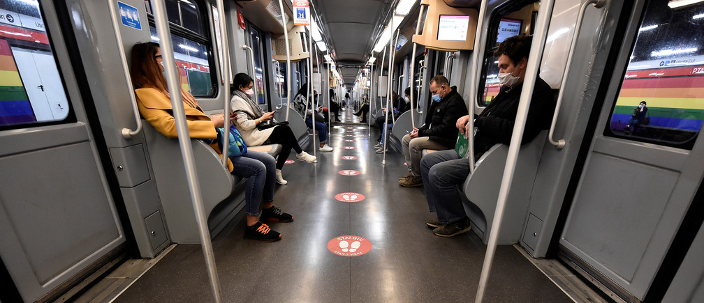 People ride a subway with social distancing signs on a floor inside a train as the spread of the coronavirus disease (COVID-19) continues, in Milan, Italy, April 27, 2020. REUTERS/Flavio Lo Scalzo - RC2ZCG9YRIYV