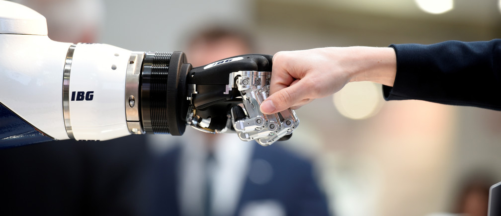 A visitor fist bumps a humanoid robot at the booth of IBG at Hannover Messe, the trade fair in Hanover, Germany, April 23, 2018. REUTERS/Fabian Bimmer - RC142BBE3900