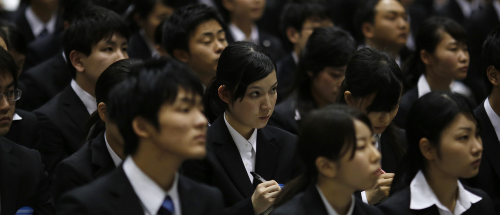 A job seeker listening to a presentation by a company employee takes notes during a job fair held for fresh graduates in Tokyo March 8, 2015.