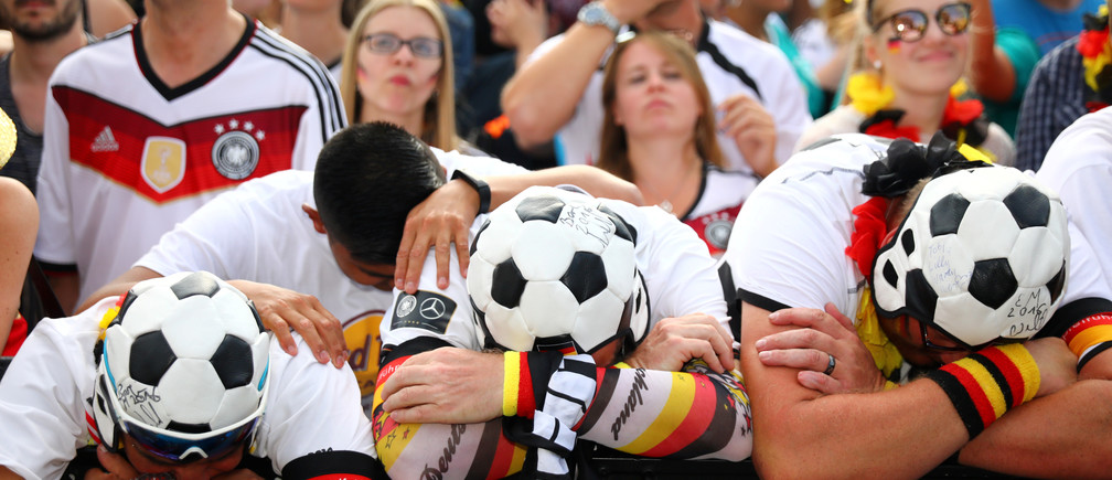 Soccer Football - World Cup - Group F - South Korea v Germany - Berlin, Germany - June 27, 2018 - Germany fans react as they watch the match at a public viewing area at Brandenburg Gate. REUTERS/Hannibal Hanschke     TPX IMAGES OF THE DAY - RC12FBBBA6D0