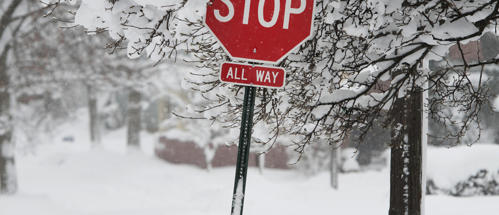 A stop sign is surrounded by record-breaking snowfall that had already surpassed 5 feet (1.5 meters), breaking city and state records, according to the National Weather Service in Erie, Pennsylvania, U.S., December 27, 2017.  REUTERS/Robert Frank - RC1264C80420