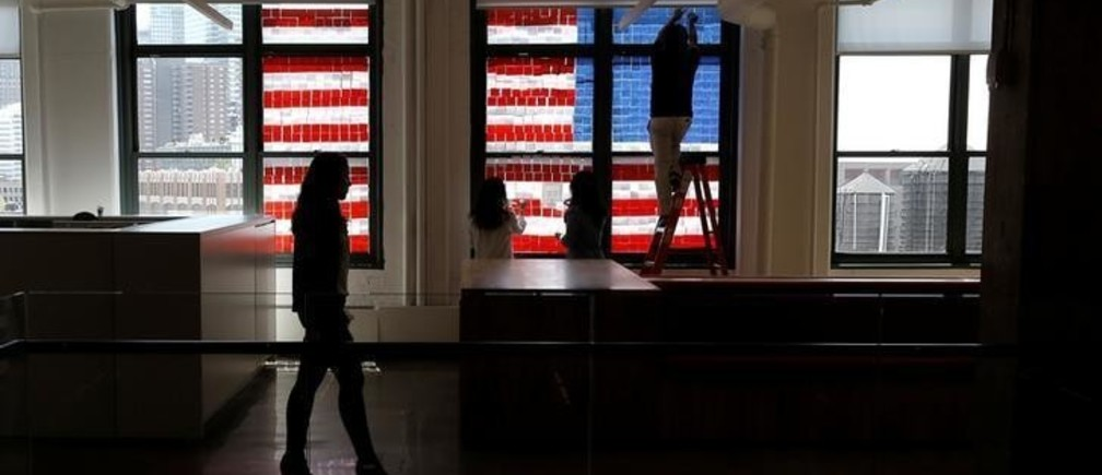 """Employees create a U.S. flag image on a window with Post-it notes at the Horizon Media offices at 75 Varick Street in lower Manhattan, New York, U.S., May 18, 2016, where advertising agencies and other companies have started what is being called a """"Post-it note art war"""" with employees in buildings across Canal street from each other creating colorful images in their windows with Post-it notes. REUTERS/Mike Segar"""