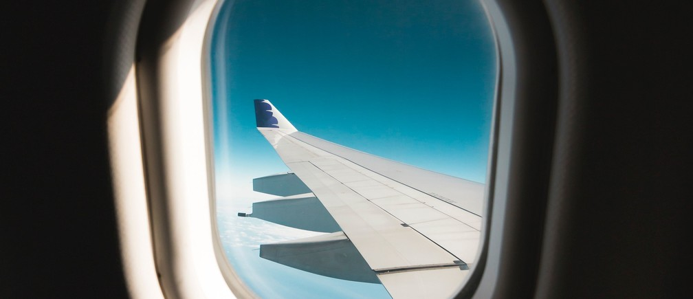 A view of a plane wing through the window of the plane