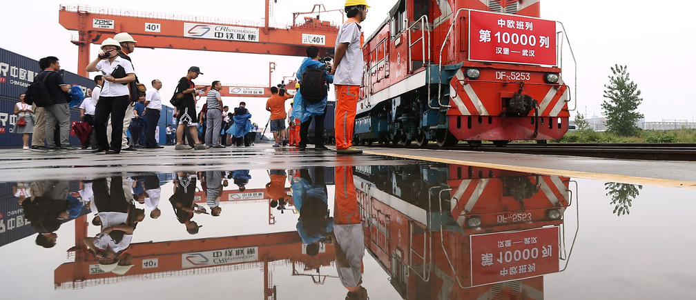 People are seen next to a China-Europe freight train that completes its 10,000th trip as it returns from Hamburg, Germany to Wuhan, Hubei province, China August 26, 2018. Picture taken August 26, 2018. China Daily via REUTERS   ATTENTION EDITORS - THIS IMAGE WAS PROVIDED BY A THIRD PARTY. CHINA OUT. - RC1C4FDCD000