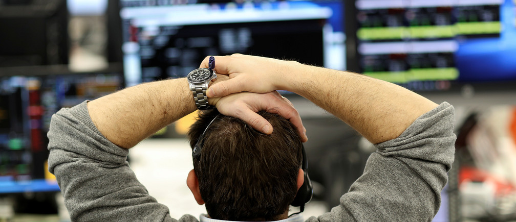 A broker looks at financial information on computer screens on the IG Index trading floor in London, Britain February 6, 2018. REUTERS/Simon Dawson - RC13323AD440