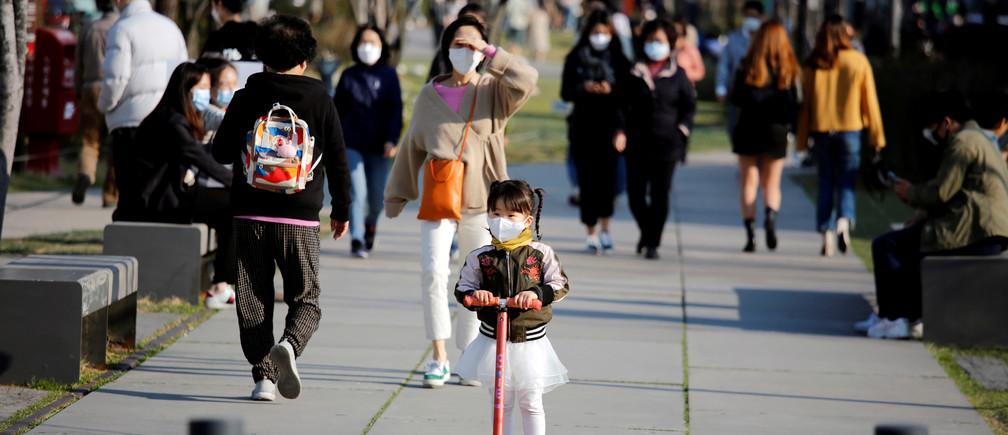 Una niña que lleva una máscara protectora para evitar contraer la enfermedad del coronavirus (COVID-19) monta un patinete de juguete en un parque de Seúl, Corea del Sur, el 3 de abril de 2020.