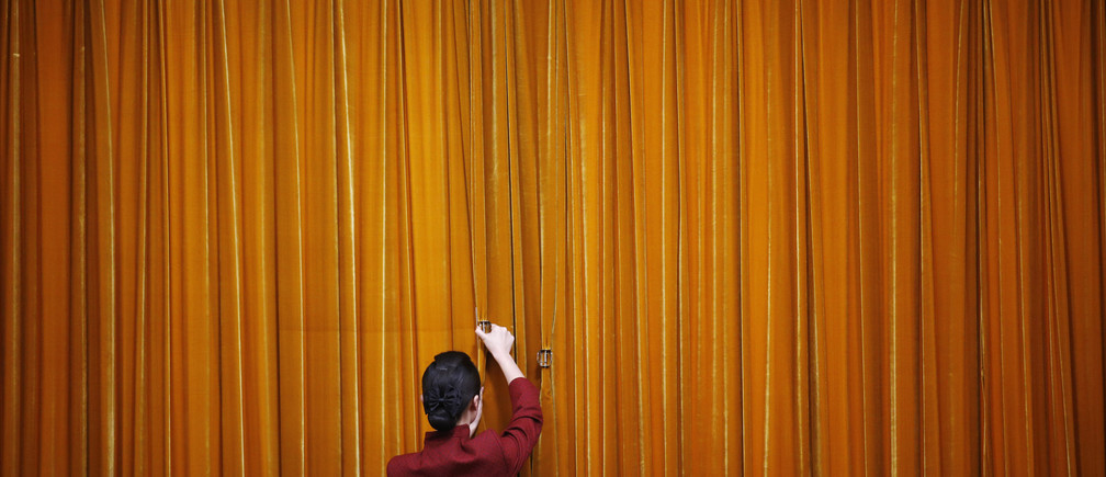An attendant puts clamps on a curtain inside the Great Hall of the People during the closing ceremony of the Chinese People's Political Consultative Conference (CPPCC) in Beijing, March 12, 2014. REUTERS/Kim Kyung-Hoon (CHINA - Tags: POLITICS TPX IMAGES OF THE DAY) - GM1EA3C0Q4G02