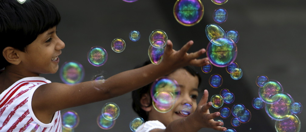 Migrant children play with bubbles at Keleti railway station in Budapest, Hungary, September 6, 2015.