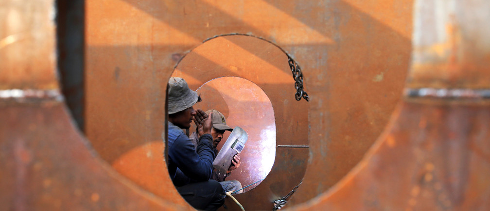Workers weld iron sheets as they build a new ferry at a dockyard in Dhaka, Bangladesh, February 7, 2019