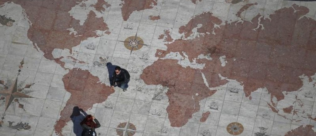 A man is photographed on a square decorated with a giant world map, with marks showing former Portuguese colonies, in Lisbon March 6, 2012. Portugal flourished as a global power with explorers like Vasco da Gama and Pedro Alvares Cabral building an empire which lasted for 600 years. Now a new wave of adventurers is once again seeking work, and hopefully fortune, elsewhere. Emigrating is fast becoming a preferred option for many seeking a decent living as their bailed-out economy suffers under debt, low growth and poor competitiveness. Portugal's booming ex-colonies in Africa and Brazil are a natural choice. Picture taken March 6, 2012. To match Feature PORTUGAL/EMIGRATION  REUTERS/Rafael Marchante (PORTUGAL - Tags: BUSINESS SOCIETY IMMIGRATION) - GM1E83E1SNS01