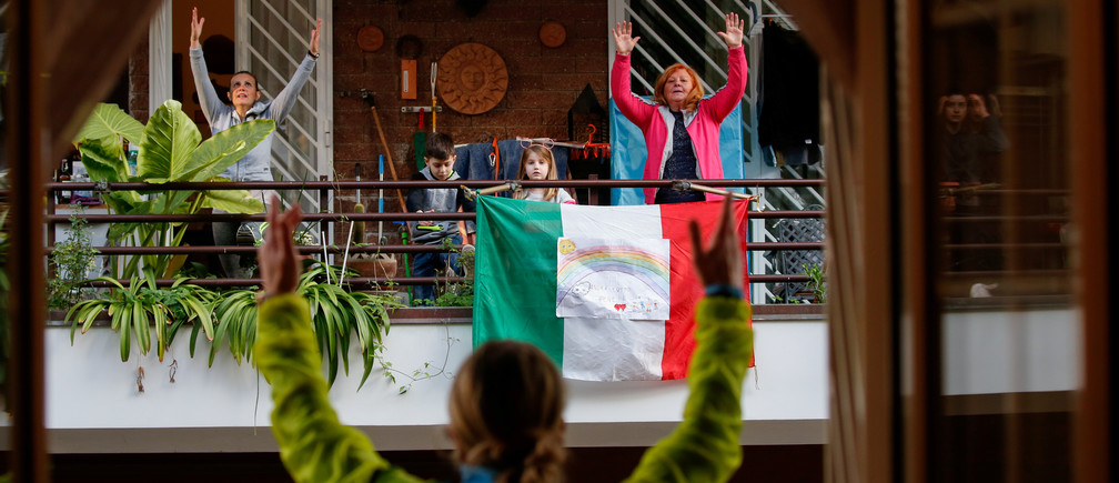 Personal trainer Antonietta Orsini carries out an exercise class for her neighbours from her balcony while Italians cannot leave their homes due to the coronavirus disease (COVID-19) outbreak, in Rome, Italy, March 18, 2020. Picture taken March 18, 2020 REUTERS/Remo Casilli     TPX IMAGES OF THE DAY - RC2WMF9RAEOP