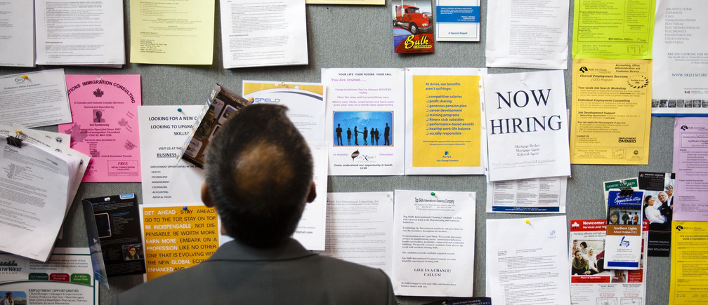 A man looks at a job board at a job fair in Toronto, April 1, 2009.      REUTERS/Mark Blinch (CANADA BUSINESS) - GM1E5420DT701