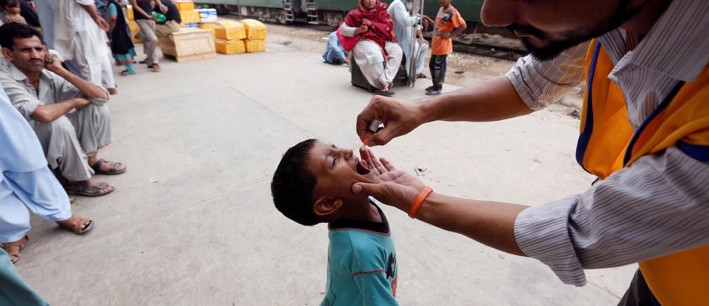 A boy receives polio vaccine drops at Cantonment Railway Station in Karachi, Pakistan, July 25, 2016. REUTERS/Akhtar Soomro - RTSJI8Q