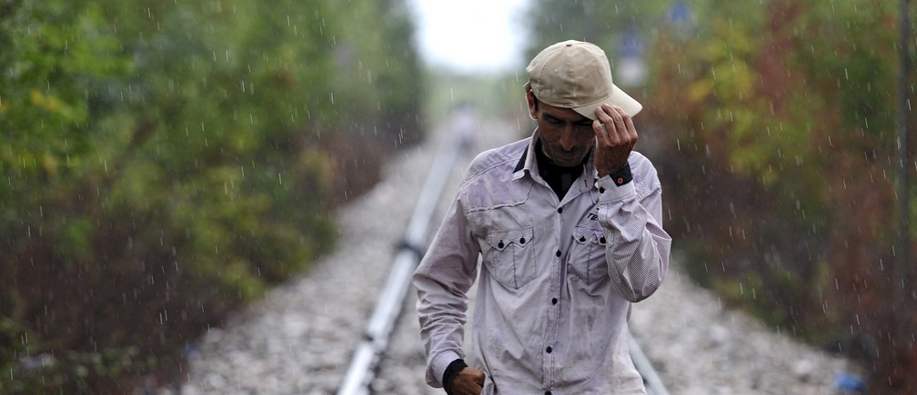 A migrant walks towards Gevgelija in Macedonia after crossing Greece's border, Macedonia, August 22, 2015. Thousands of migrants stormed across Macedonia's border on Saturday, overwhelming security forces who threw stun grenades and lashed out with batons in a