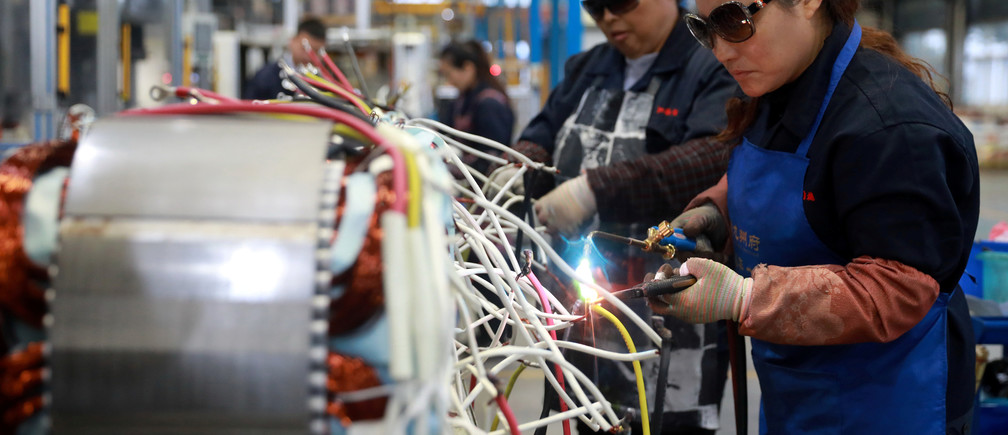 Women wearing sunglasses work at a production line manufacturing electric machine parts at a factory in Luan, Anhui province, China November 17, 2018. Picture taken November 17, 2018. REUTERS/Stringer ATTENTION EDITORS - THIS IMAGE WAS PROVIDED BY A THIRD PARTY. CHINA OUT. - RC11E1AB4D40