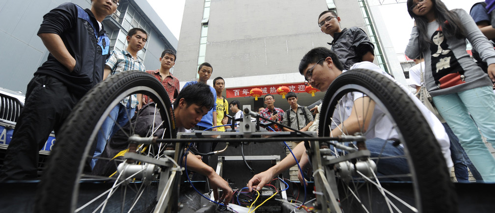 Chinese students check the battery of a new fuel-efficient vehicle.